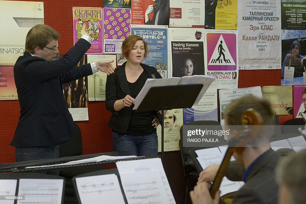 Singer Iris Oja (C) performs with members of the Tallinn Chamber Orchestra and their conductor Risto Joost (L) during a rehearsal of the opera 'Nostra Culpa' on April 3, 2013 in Tallinn, Estonia. US composer Eugene Birman turned into an opera a Twitter feud between the Estonian President Toomas Hendrik Ilves and New York Times columnist Paul Krugman who questioned the impact of Estonia's austerity measures. The short opera in two movements and using two voices will be first performed during Tallinn Music Week on April 7, Birman, who moved from Riga to the US at age of six, told AFP. AFP PHOTO / RAIGO PAJULA