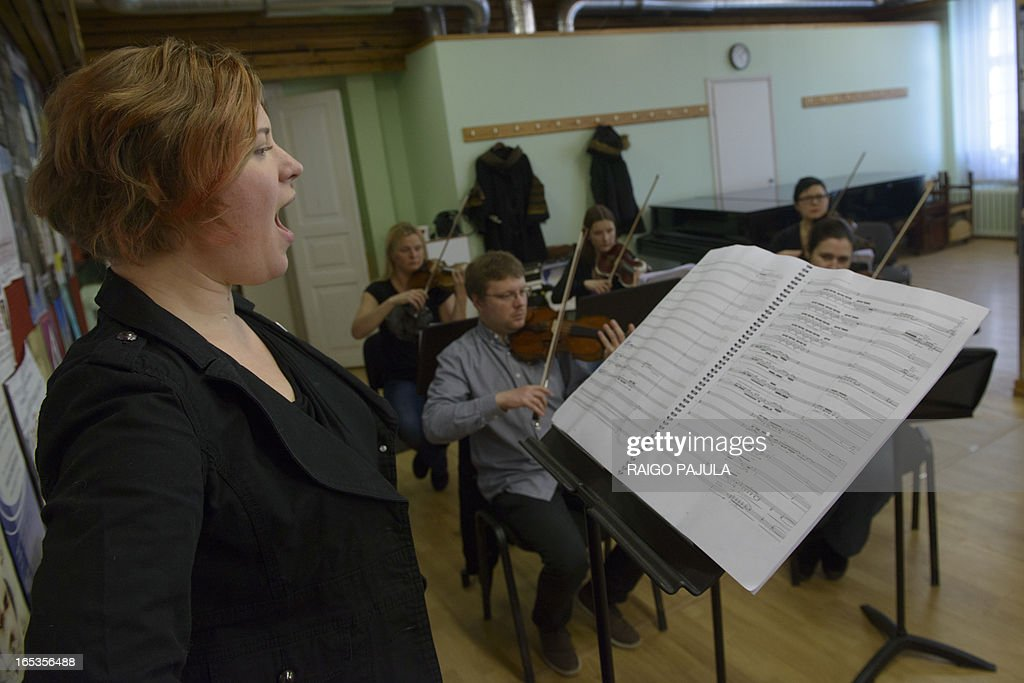 Singer Iris Oja (L) performs with members of the Tallinn Chamber Orchestra during a rehearsal of the opera 'Nostra Culpa' on April 3, 2013 in Tallinn, Estonia. US composer Eugene Birman turned into an opera a Twitter feud between the Estonian President Toomas Hendrik Ilves and New York Times columnist Paul Krugman who questioned the impact of Estonia's austerity measures. The short opera in two movements and using two voices will be first performed during Tallinn Music Week on April 7, Birman, who moved from Riga to the US at age of six, told AFP. AFP PHOTO / RAIGO PAJULA