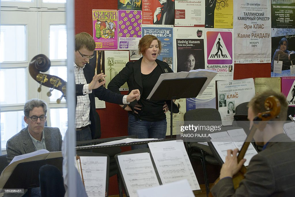 Singer Iris Oja (C) performs with members of the Tallinn Chamber Orchestra, their conductor Risto Joost (2nd L) and Scott Diel (L, seen in the mirror), author of the libretto, during a rehearsal of the opera 'Nostra Culpa' on April 3, 2013 in Tallinn, Estonia. US composer Eugene Birman turned into an opera a Twitter feud between the Estonian President Toomas Hendrik Ilves and New York Times columnist Paul Krugman who questioned the impact of Estonia's austerity measures. The short opera in two movements and using two voices will be first performed during Tallinn Music Week on April 7, Birman, who moved from Riga to the US at age of six, told AFP.