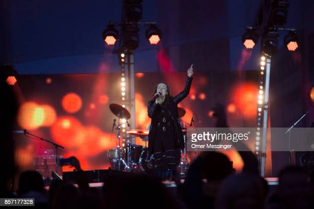 A singer is seen on stage at an amusement area set up along 17th of June Street in Tiergraten Park near the Brandenburg Gate on German Unity Day on...