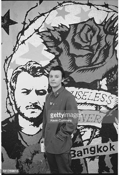 Singer James Dean Bradfield of Welsh alternative rock group the Manic Street Preachers posing in front of a portrait of himself on a poster...