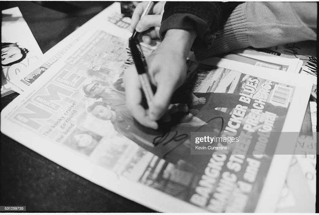 Singer James Dean Bradfield of Welsh alternative rock group the Manic Street Preachers signs a copy of the NME whose cover features the band Los...