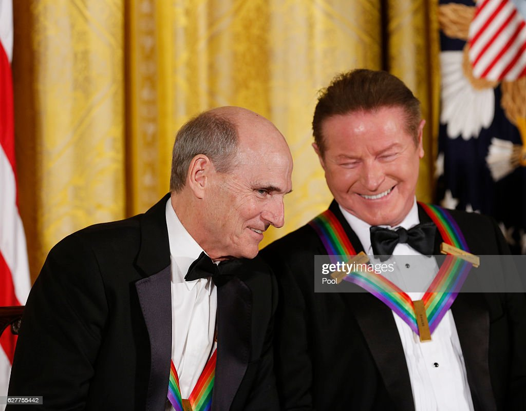 Singer James Taylor and Eagles band member Don Henley listen to President Barack Obama speak during a ceremony for the 2016 Kennedy Center honorees December 4, 2016 in the East Room of the White House in Washington, DC. The honorees include Eagles band members, actor Al Pacino, singer James Taylor, pianist Martha Argerich and singer Mavis Staples.