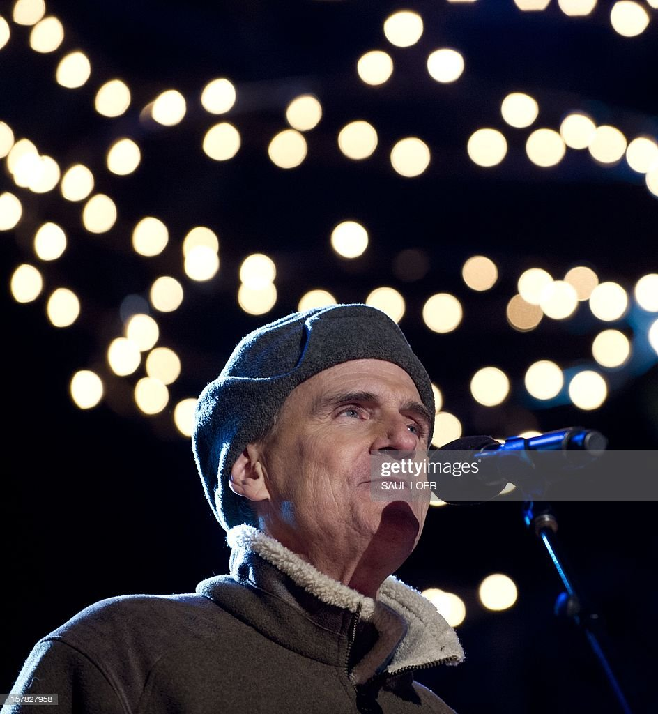 Singer James Taylor performs during the National Christmas Tree Lighting on the Ellipse adjacent to the White House in Washington, DC, on December 6, 2012. The annual event, hosted by Actor Neil Patrick Harris, features US President Barack Obama and performances by Jason Mraz, Ledisi, James Taylor, Kenny 'Babyface' Edmonds, Colbie Caillat and American Idol season 11 winner Phillip Phillips. AFP PHOTO / Saul LOEB
