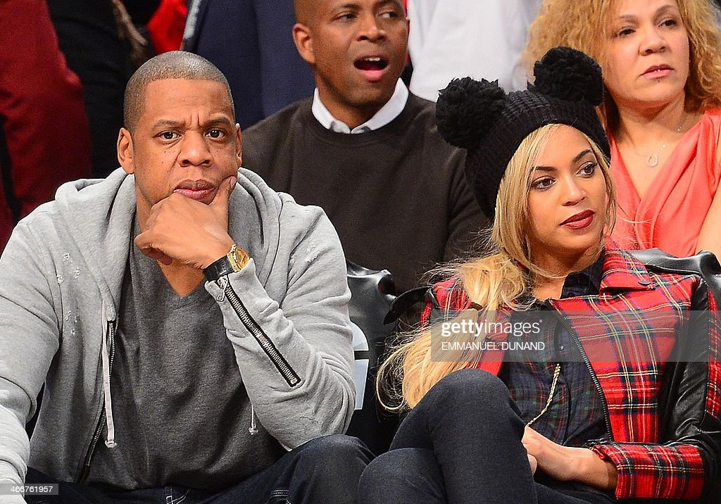 Singer Jay Z and his wife singer Beyonce watch the NBA game between the Philadelphia 76ers and the Brooklyn Nets at the Barclays Center in New York, February 3, 2014 AFP PHOTO/Emmanuel Dunand