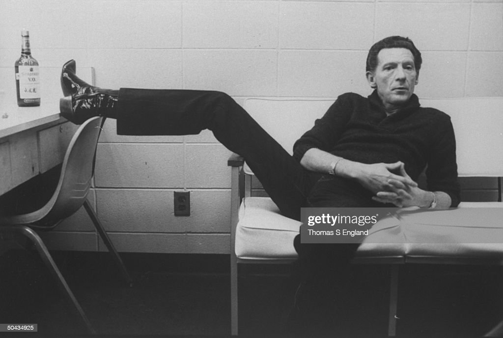 Singer Jerry Lee Lewis lounging on couch w. one foot up on dressing table next to a bottle of Seagram's V.O. whiskey in dressing room at Performing Arts Center.