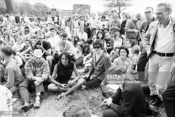Singer Joan Baez and singer songwriter Donovan in the audience front row at the Newport Folk Festival in July 1965 in Newport Rhode Island