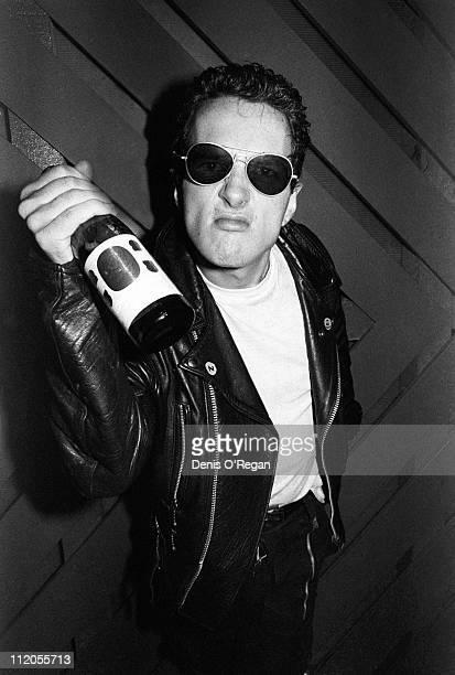 Singer Joe Strummer of English punk group The Clash brandishing a bottle London 1977