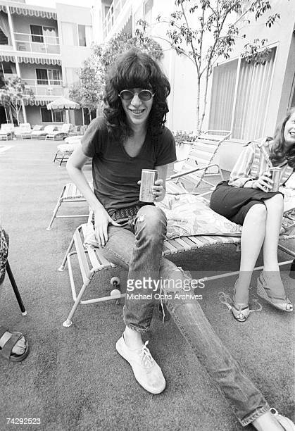 Singer Joey Ramone of the punk band 'The Ramones' drinks a can of Michelob beer as he lounges poolside at a hotel in circa 1977 in Los Angeles...