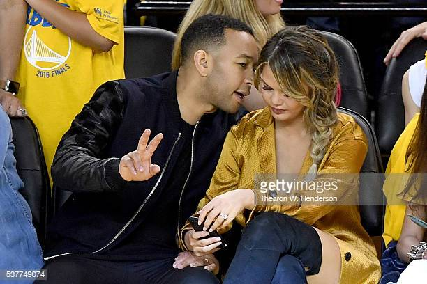 Singer John Legend with wife/model Chrissy Teigen sit courtside in Game 1 of the 2016 NBA Finals at ORACLE Arena on June 2 2016 in Oakland California...