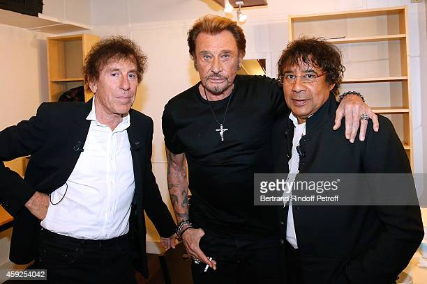 Singer Johnny Hallyday standing between Main Guests of the show singers Alain Souchon and Laurent Voulzy attend the 'Vivement Dimanche' French TV...