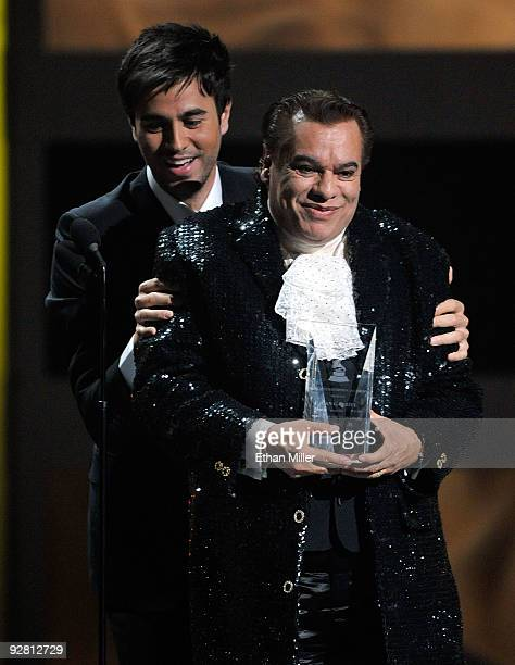 Singer Juan Gabriel accepts the Person of the Year award from singer Enrique Iglesias onstage during the 10th annual Latin GRAMMY Awards held at...