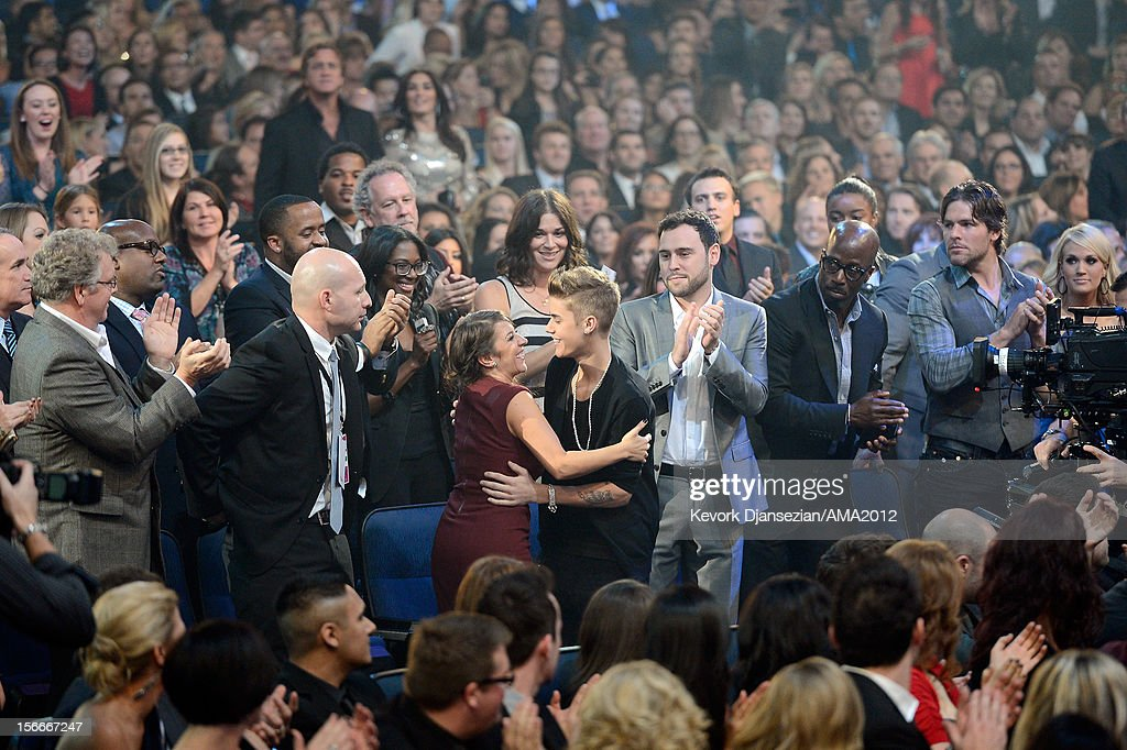 Singer Justin Bieber and mother Pattie Malette hug in the audience at the 40th American Music Awards held at Nokia Theatre LA Live on November 18...