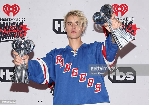 Singer Justin Bieber winner of the awards for Best Male Artist and Dance Song of the Year poses in the press room during the iHeartRadio Music Awards...