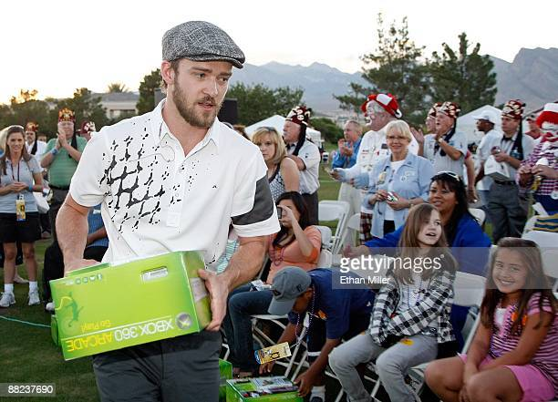 Singer Justin Timberlake hands out Xbox 360 video game consoles to youth from Shriners Hospitals during a golf clinic for kids during the Justin...