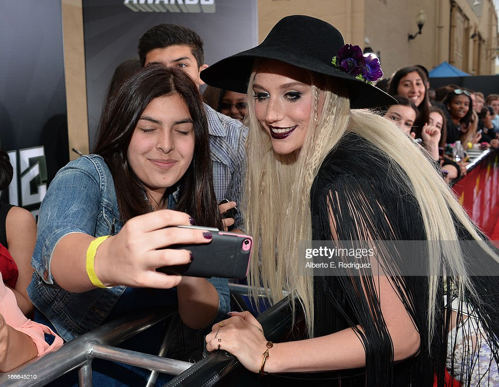Singer Ke$ha (R) arrives at the 2013 MTV Movie Awards at Sony Pictures Studios on April 14, 2013 in Culver City, California.
