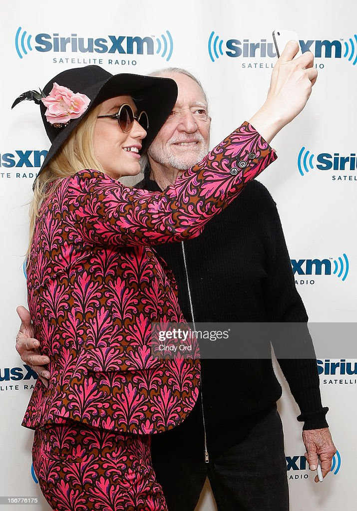 Singer Ke$ha takes an instagram photo with singer Willie Nelson at the SiriusXM Studios on November 20, 2012 in New York City.