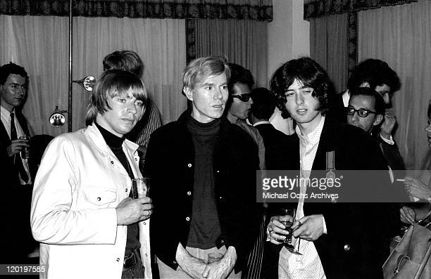 Singer Keith Relf and guitarist Jimmy Page of the rock band 'The Yardbirds' chat with Andy Warhol at the press party announcing that Page will join...