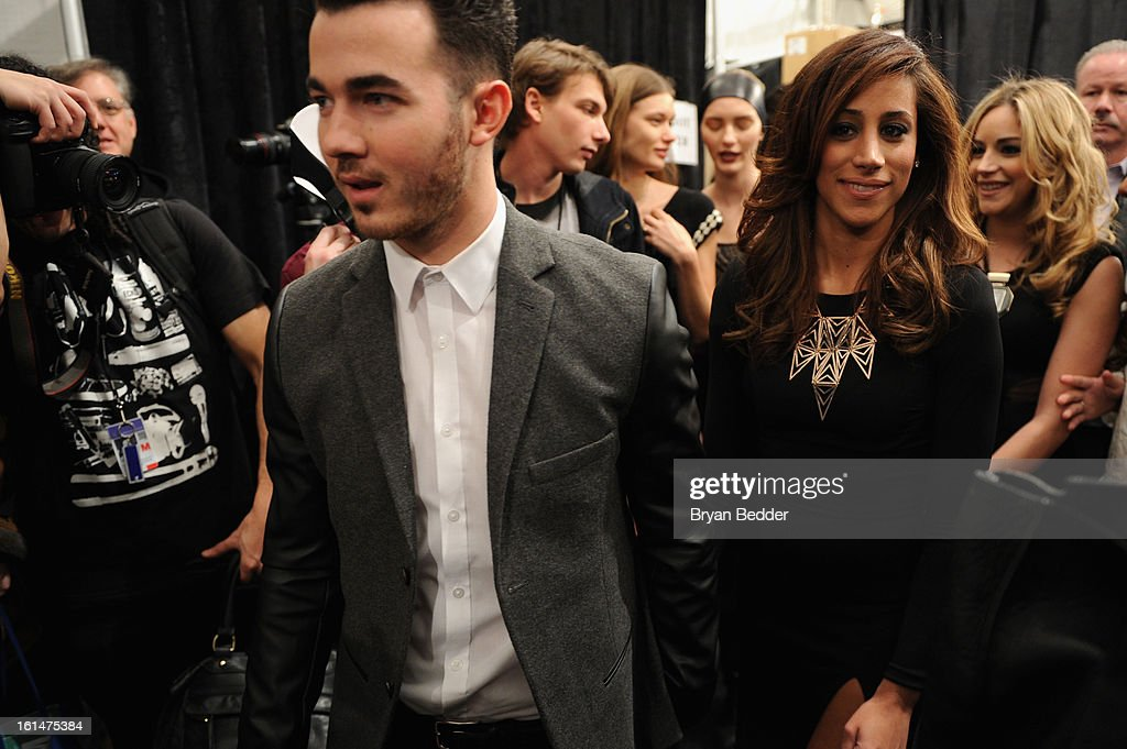 Singer Kevin Jonas and his wife Danielle Deleasa walk backstage at the Pamella Roland 2013 Fall fashion show during Fall 2013 Mercedes-Benz Fashion Week at Lincoln Center for the Performing Arts on February 11, 2013 in New York City.