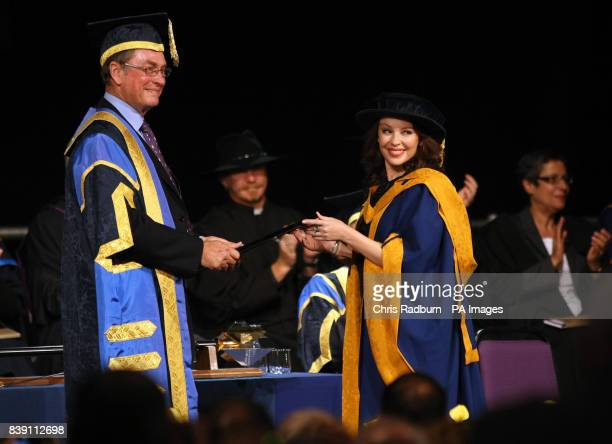 Singer Kylie Minogue smiles as she receives her honorary degree from University Chancellor Lord Ashcroft at Anglia Ruskin University in Chelmsford...