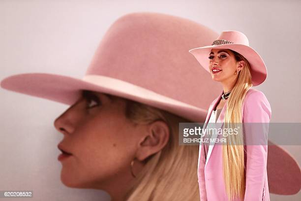 Singer Lady Gaga poses for the photographers in front of her new album cover during a photo call to promote the album 'Joanne' in Tokyo on November 2...