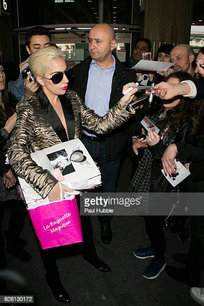 Singer Lady Gaga signs autographs as she arrives at Aeroport Roissy Charles de Gaulle on November 27 2016 in Paris France