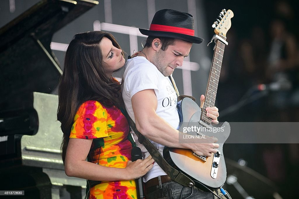 US singer Lana Del Rey (L) interacts with her guitarist as she performs on the Pyramid Stage, on the second day of the Glastonbury Festival of Music and Performing Arts in Somerset, southwest England, on June 28, 2014. US metal giants Metallica will play this year's coveted Saturday night headline spot at Britain's Glastonbury festival, organisers announced Thursday. It will be the 'Master of Puppets' four-piece's first appearance at the legendary festival, held in south west England, following on from The Rolling Stones' Worthy Farm debut last year.