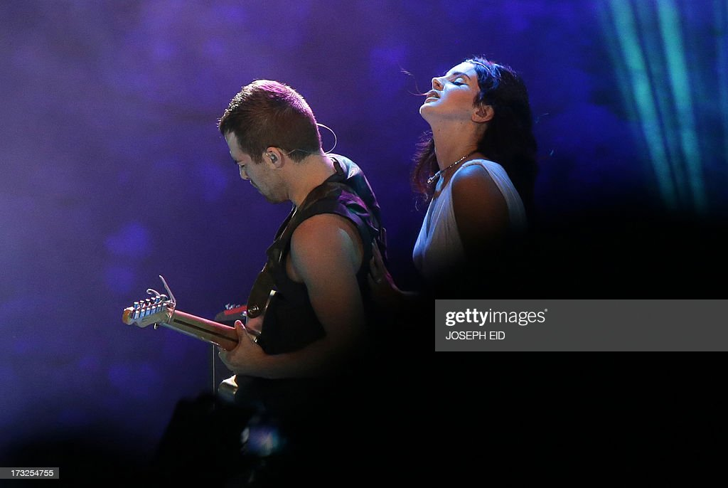 US singer Lana Del Rey performs on stage near a musician during a concert as part of the Byblos music festival on July 10, 2013 in the coastal city of Byblos, north of Beirut. The festival runs until July 27. AFP PHOTO/JOSEPH EID