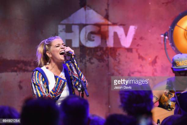 Singer Lauren Alaina performs with a young fan onstage at the HGTV Lodge during CMA Music Fest on June 11 2017 in Nashville Tennessee