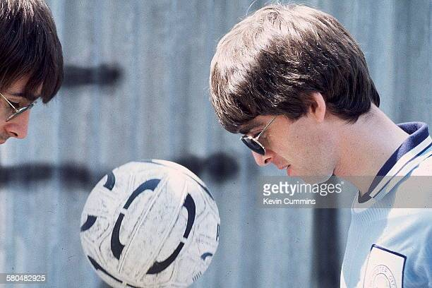 Singer Liam Gallagher and his guitarist brother Noel Gallagher of rock band Oasis with a football 9th May 1994