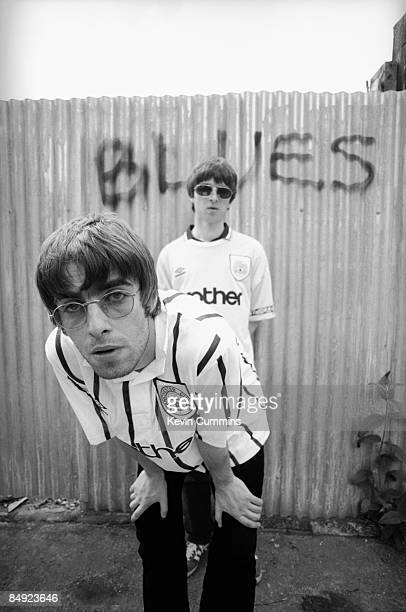 Singer Liam Gallagher and his guitarist brother Noel Gallagher of rock band Oasis pose in Manchester City football shirts 9th May 1994 The football...