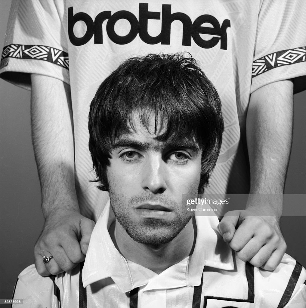 Singer Liam Gallagher of British rock group Oasis in a Manchester City shirt, Portsmouth, 9th May 1994. Standing behind him is his brother Noel.