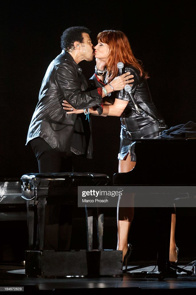 US singer Lionel Richie (L) and German singer Andrea Berg (R) kiss after singing together at the Arena on October 22, 2012 in Leipzig, Germany.