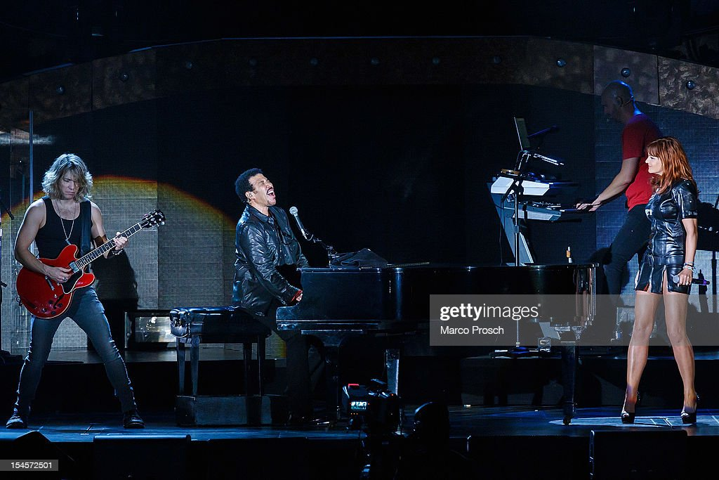 US singer Lionel Richie (C) and German singer Andrea Berg (R) perform live together at the Arena on October 22, 2012 in Leipzig, Germany.