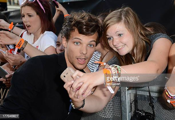 Singer Louis Tomlinson from One Direction poses with fans as he attends the 'One Direction This Is Us' world premiere at the Empire Leicester Square...