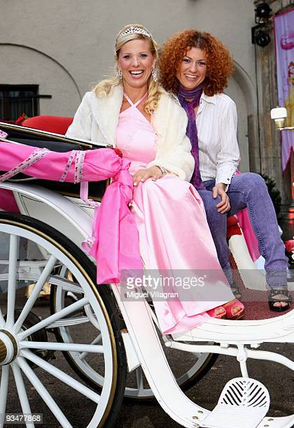 Singer Lucy Diakovska and Princess Maja von Hohenzollern sit in a carriage and pose during the premiere of the Disney film 'Kiss the frog' on...