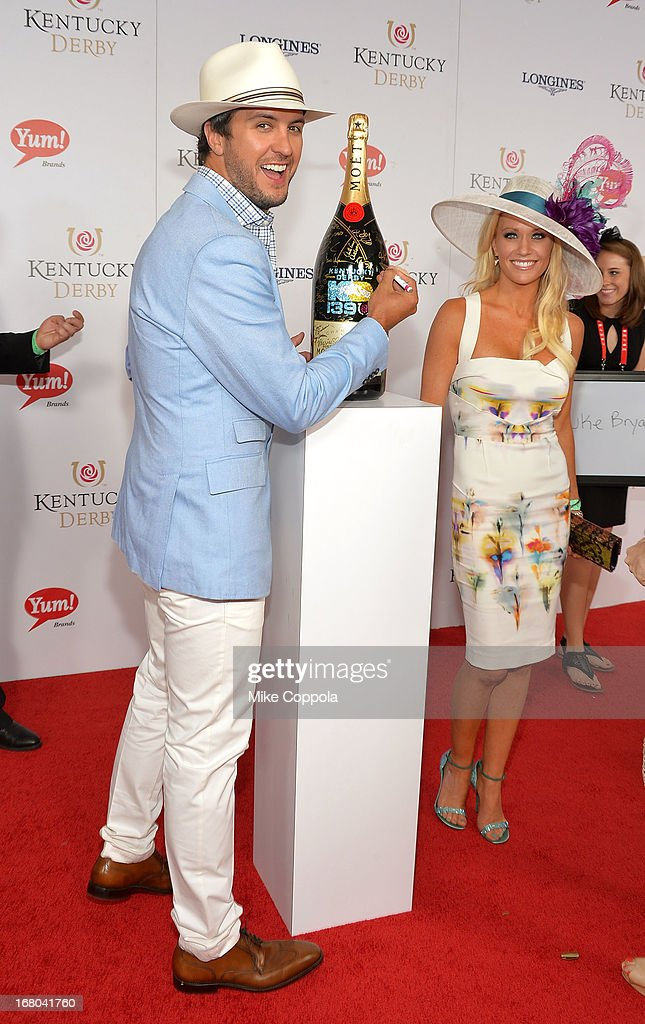 Singer Luke Bryan and wife Caroline Boyer sign the Moet & Chandon 6L for the Churchill Downs Foundation during the 139th Kentucky Derby at Churchill Downs on May 4, 2013 in Louisville, Kentucky.