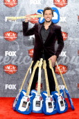 Singer Luke Bryan poses in the press room with multiple awards during the 2012 American Country Awards at the Mandalay Bay Events Center on December...