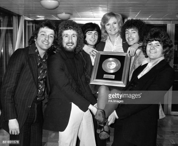 Singer Lyn Paul is given a lift up by the pop group Paper Lace while she exhibits an award the group gained two gold record awards for the Australian...
