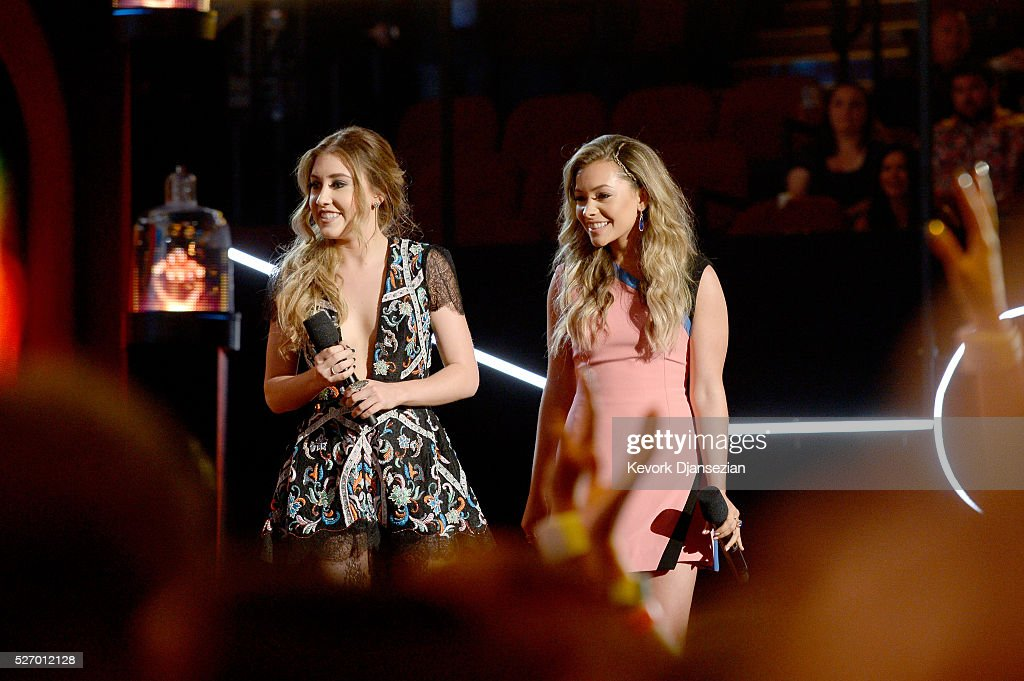 Singer Maddie Marlow (L) and Tae Dye speak onstage during the 2016 American Country Countdown Awards at The Forum on May 1, 2016 in Inglewood, California.
