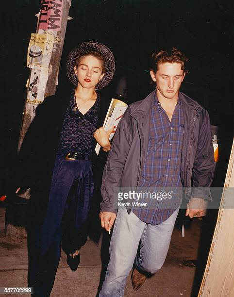 Singer Madonna and her husband actor Sean Penn walking along a street together circa 1988