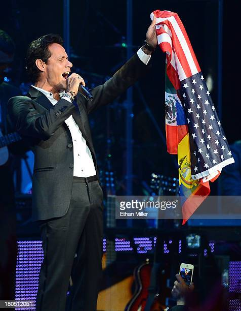 Singer Marc Anthony performs while holding a gift from a fan made up of flags of the United States Ecuador Puerto Rico and Mexico all joined together...