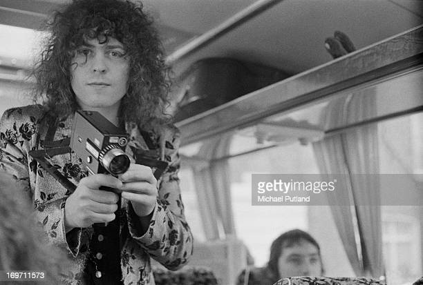 Singer Marc Bolan of English glam rock group TRex holding a cine camera on a tour bus during a fourdate British tour June 1972