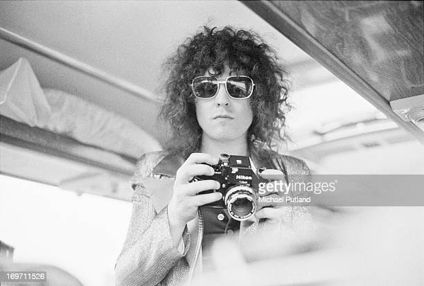 Singer Marc Bolan of English glam rock group TRex holding a Nikon camera on a tour bus during a fourdate British tour June 1972