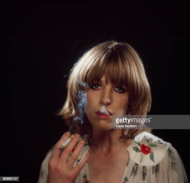 Singer Marianne Faithfull blows smoke from her mouth as she poses in a dress by Ossie Clark in 1973