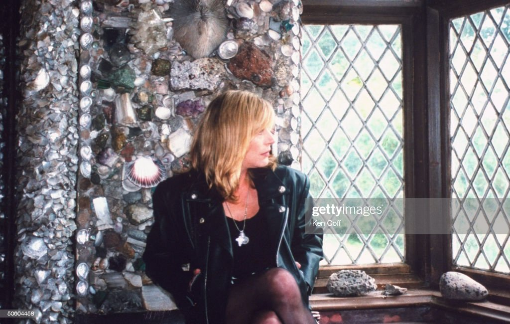 Singer Marianne Faithfull wearing black leather jacket as she sits looking out leaded window in rm. w. wall & ceiling decorated w. rows & patterns of seashells set in stucco work, in her 19th C. cottage.