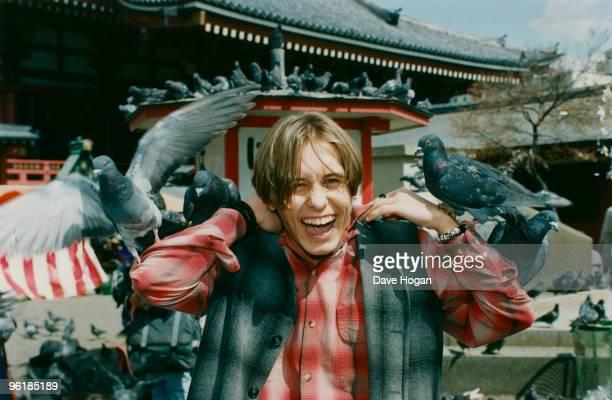 Singer Mark Owen of English boy band Take That is beset by pigeons during a visit to Japan circa 1995