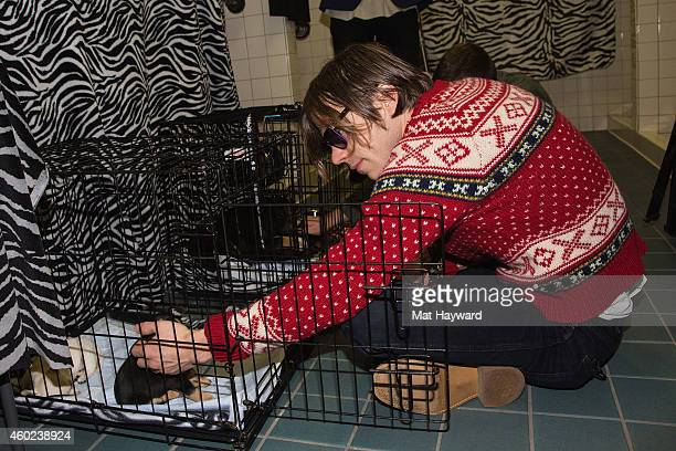 Singer Matt Shultz of Cage The Elephant plays with a puppy brought by Motley Zoo Animal Rescue backstage during Deck the Hall Ball hosted by 1077 The...