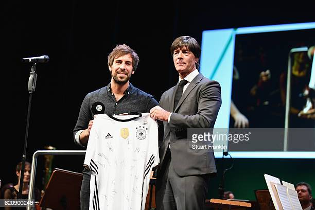 Singer Max Giesinger and head coach of the German National Team Joachim Loew show a signed jersey of the German National Team during the ceremonial...