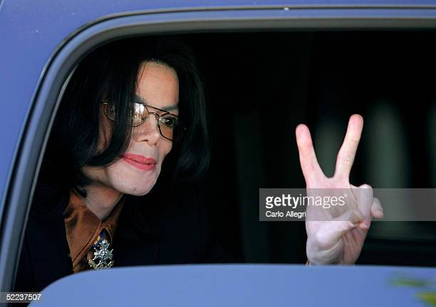 Singer Michael Jackson flashes a 'V' sign to fans from inside a vehicle as he departs the Santa Barbara County Courthouse following the jury...